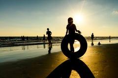 Силуэт девушки играя на пляже Стоковое Изображение
