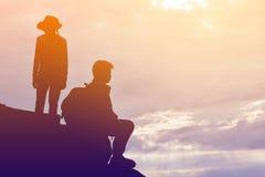 Силуэт девушки и мальчика на утесе Стоковая Фотография