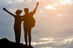Силуэт девушки и мальчика на утесе Стоковое Изображение RF