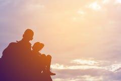 Силуэт девушки и мальчика на утесе Стоковое фото RF
