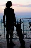 Силуэт девушки и ребенка на предпосылке моря и th Стоковые Фотографии RF
