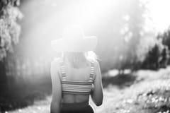 Силуэт девушки идя в парк внешний Солнечная концепция образа жизни лета Женщина в платье и шляпе в поле с Стоковое Фото