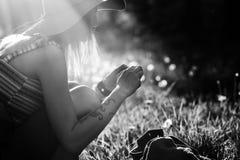Силуэт девушки идя в парк внешний Солнечная концепция образа жизни лета Женщина в платье и шляпе в поле с Стоковые Изображения