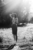Силуэт девушки идя в парк внешний Солнечная концепция образа жизни лета Женщина в платье и шляпе в поле с Стоковое Изображение