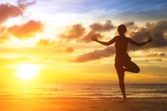 Силуэт девушки йоги на красивом пляже моря Стоковая Фотография RF