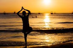 Силуэт девушки йоги на пляже моря на заходе солнца Стоковое Изображение RF