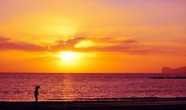 Силуэт девушки морем на заходе солнца в Alghero Стоковые Фотографии RF