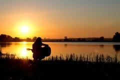 Силуэт девушки на восходе солнца играя гитару рекой Стоковые Изображения