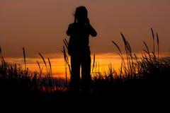 Силуэт девушки на заходе солнца в песчанных дюнах Стоковые Фотографии RF