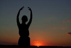 Силуэт девушки на заходе солнца стоковые фото