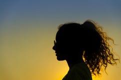 Силуэт девушки на заходе солнца Стоковые Фотографии RF