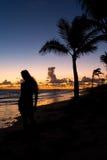 Силуэт девушки на океане на зоре Стоковые Изображения