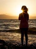 Силуэт девушки на пляже на заходе солнца Стоковое Изображение