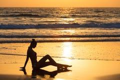 Силуэт девушки ослаблять на пляже на заходе солнца Женщина на предпосылке океана Стоковое Изображение RF