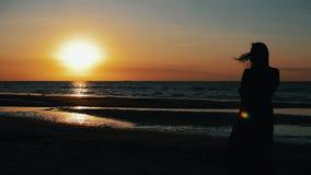 Силуэт девушки представляя к фотографу на пляже Море Photoshoot Заход солнца видеоматериал