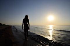 Силуэт девушки против захода солнца морем Стоковое Фото