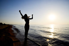 Силуэт девушки против захода солнца морем Стоковая Фотография