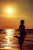 Силуэт девушки против моря захода солнца стоковое фото rf