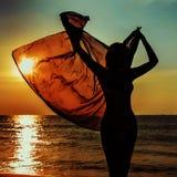 Силуэт девушки против моря захода солнца Стоковые Изображения