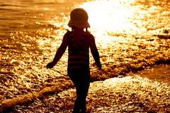 Силуэт девушки ребенка идя на пляж захода солнца Стоковое фото RF