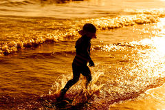 Силуэт девушки ребенка идя на пляж захода солнца Стоковая Фотография RF