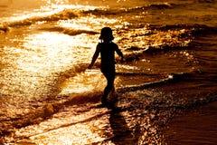Силуэт девушки ребенка идя на пляж захода солнца Стоковые Изображения RF
