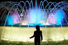Силуэт девушки ребенк на красочном фонтане Стоковое Изображение RF