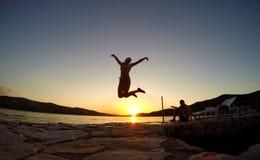 Силуэт девушки скача на заход солнца на пляже Стоковые Фотографии RF