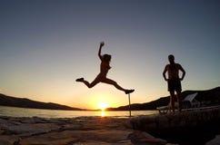 Силуэт девушки скача на заход солнца на пляже Стоковые Изображения RF
