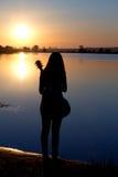 Силуэт девушки с гитарой рекой Стоковые Изображения RF