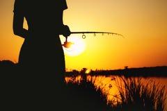 Силуэт девушки с рыболовной удочкой на речном береге на зоре Стоковое фото RF