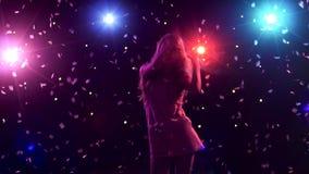 Силуэт девушки танцев с светами и confetti стиля диско акции видеоматериалы