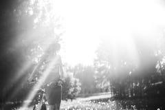 Силуэт девушки управляя велосипедом внешним Солнечная концепция образа жизни лета Женщина в платье и шляпе в поле с Стоковая Фотография