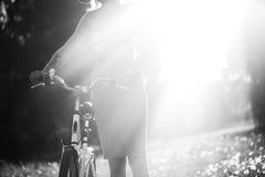 Силуэт девушки управляя велосипедом внешним Солнечная концепция образа жизни лета Женщина в платье и шляпе в поле с Стоковое фото RF