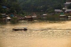 Силуэт езды шлюпки человека гребли в реке на заходе солнца в Sa Стоковые Фотографии RF
