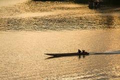 Силуэт езды шлюпки человека гребли в реке на заходе солнца в Sa Стоковые Фото