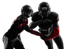 Силуэт действия проходя игры 2 американский футболистов Стоковое фото RF