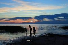 Силуэт детей на заходе солнца Стоковые Изображения RF
