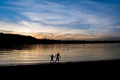 Силуэт 2 детей около озера на заходе солнца Стоковые Фото