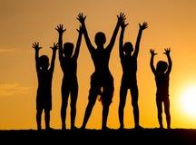 Силуэт детей против захода солнца Стоковые Изображения