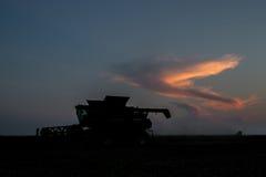 Силуэт жатки зернокомбайна работая через ночу Стоковые Фотографии RF