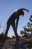 Силуэт женщины выполняя йогу при солнце светя за ей Стоковое Изображение RF