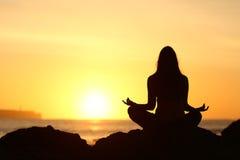 Силуэт женщины делая йогу на восходе солнца стоковые изображения