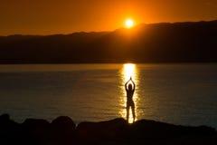 Силуэт женщины делая йогу на пляже на заходе солнца стоковая фотография rf