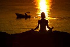 Силуэт женщины делая йогу на пляже на заходе солнца стоковое фото