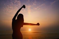 Силуэт женщины делая йогу на пляже с предпосылкой захода солнца Стоковые Изображения RF