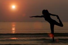 Силуэт женщины делая йогу на пляже с backgro захода солнца Стоковая Фотография RF