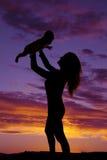 Силуэт женщины задерживая ее младенца стоковое изображение