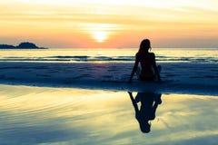 Силуэт женщины кладя на пляж моря захода солнца Стоковое Изображение