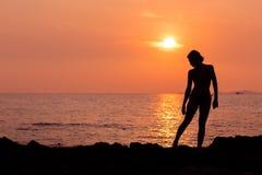 Силуэт женщины на назад освещенной предпосылке моря Стоковое Изображение